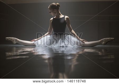 Young ballerina in white tutu sitting on the splits in the dance hall. She puts her hands on her knees. She is reflected on the floor surface. Light falls down on her from above. Low key photo.