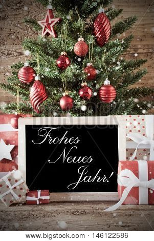 Nostalgic Christmas Card For Seasons Greetings. Christmas Tree With Balls. Gifts Or Presents In The Front Of Wooden Background. Chalkboard With German Text Frohes Neues Jahr Means Happy New Year