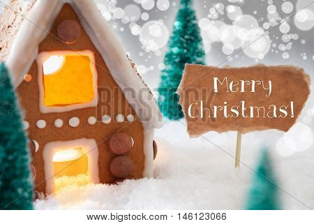 Gingerbread House In Snowy Scenery As Christmas Decoration. Christmas Trees And Candlelight For Romantic Atmosphere. Silver Background With Bokeh Effect. English Text Merry Christmas