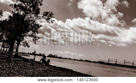 Park scene in New Orleans on the bank of the Mississippi River with ships in back