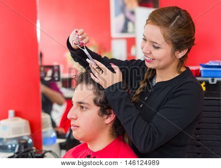 Inside a barbershop a young and nice hairstylists is cutting the hair of a man with curly hair.