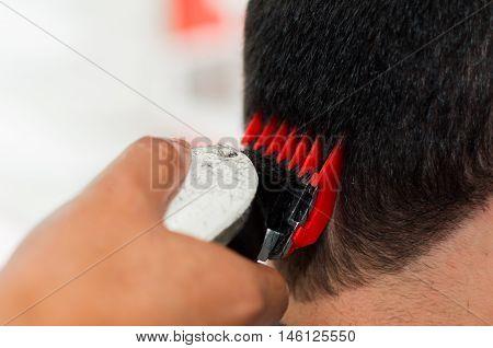 Close up of red machine cutting a man hair, short hair.