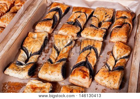 Sweet Pastry, Puff Pastry With Poppy Filling On Shelf In Bakery Shop. Pastries And Bread In A Bakery