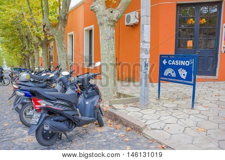COLONIA DEL SACRAMENTO, URUGUAY - MAY 04, 2016: some motorcycles parked in the street close to a casino sign located in a corner.