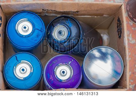 PUNTA DEL ESTE, URUGUAY - MAY 06, 2016: empty spray cans inside a box after using them.