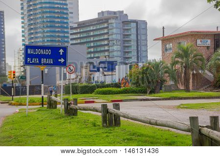 PUNTA DEL ESTE, URUGUAY - MAY 06, 2016: blue metal sign indicating the directions to the beach in the street with some buildings as background.