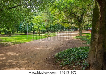PORTO ALEGRE, BRAZIL - MAY 06, 2016: bench at the side of a small road inside a park surrounded by trees.