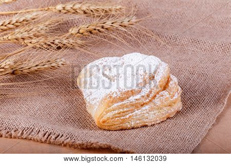 Fresh Puff Pastry With Powdered Sugar On Rustic Background With Spikelets