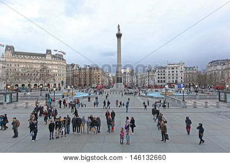 LONDON UNITED KINGDOM - JANUARY 27: Tourists at Trafalgar Square in London on JANUARY 27 2013. Lot of Tourists at Trafalgar Square in London United Kingdom.