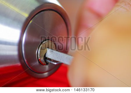 Closeup hands of locksmith using metal pick tools to open locked door.