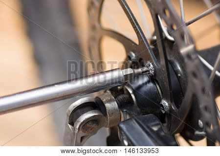 Closeup multi screwdriver working on mechanical parts next to wheel spokes.