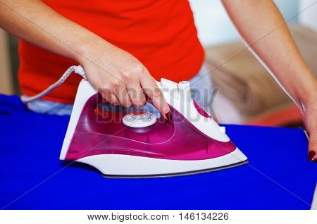 Closeup womans hands using ironing device on blue fabric, laundry housework concept.