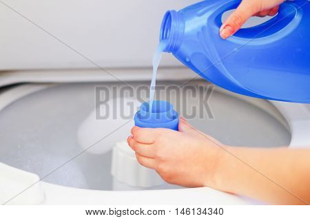 Closeup womans hands pouring detergent into to measure cup for washing machine, laundry housework concept.
