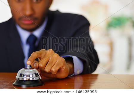 Man wearing elegant blue suit pressing desk bell at hotel reception.