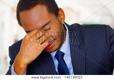 Man wearing elegant blue business suit bending head forward into fingers of right hand, frustrated body language.