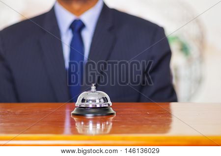 Elegant blue business suit standing behind desk bell at hotel reception.