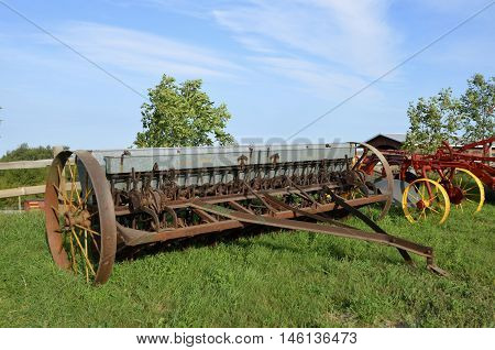 An old grain drill with a metal box to hold seed for planting small grain is parked in the grass.