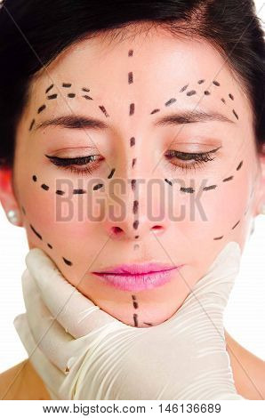 Headshot caucasian woman with dotted lines drawn around face looking into camera, doctors hands holding her head, preparing cosmetic surgery.