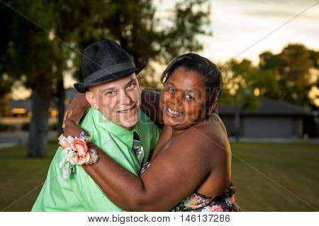 A happy interracial couple poses for a portrait before an adult prom. She is wearing a corsage.