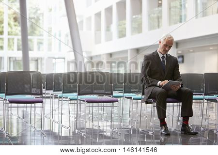 Businessman In Empty Auditorium Preparing To Make Speech
