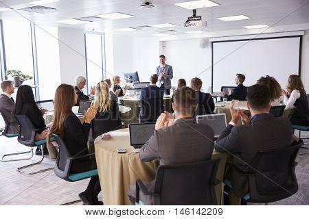 Delegates Applauding Businessman Making Presentation