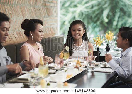 Preteen girl having lunch with her family