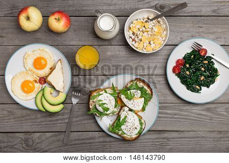 Helpful and tasty breakfast - fried egg apple avocado cheese sandwiches poached eggs spinach salad muesli milk and orange juice on a wooden table top view