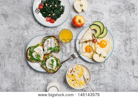 Helpful and tasty breakfast from different of dishes - fried egg poached eggs avocado apple spinach salad muesli milk cheese sandwiches and orange juice on light surface top view