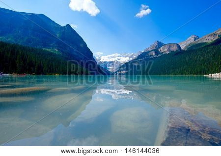 Rocks at alpine lake and mountains. Lake Louise.  Banff National Park. Rocky Mountains. Alberta. Canada.