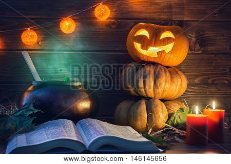 Happy halloween! Head pumpkin, candles, spell book and potion on wooden background.