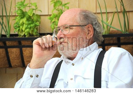Mature country gentleman relaxing on patio deck at home.