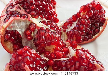 juicy lobules of garnet on plate and wood background