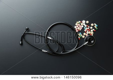 Stethoscope and pills on black table. Top view.