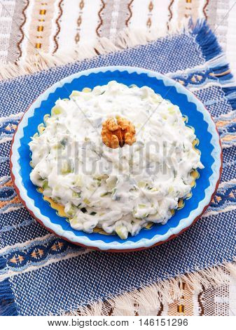 Tzatziki is appetizer from the Greek cuisine made of strained yogurt with cucumbers garlic and fresh green herbs