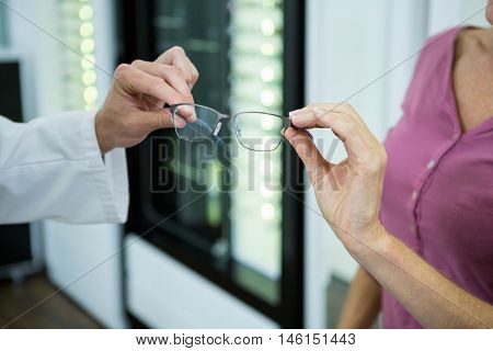 Mid section of optometrist giving spectacles to customer in optical store