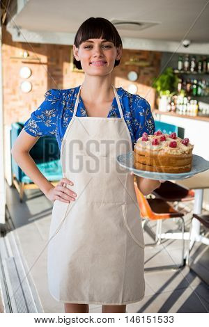Portrait of smiling waitress holding a cake in the cake shop