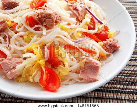 Rice noodle salad with tuna fish and cherry tomatoes. Horizontal shot