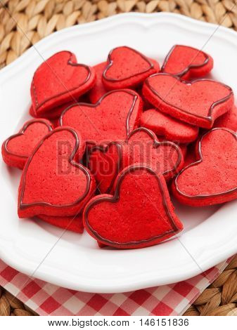 Homemade heart-shaped red cookies decorated with chocolate frosting. Vertical shot