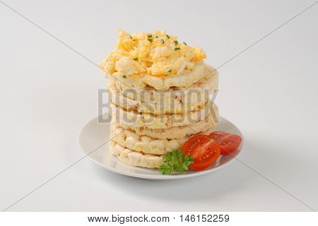 slices of puffed rice bread with scrambled eggs on white plate