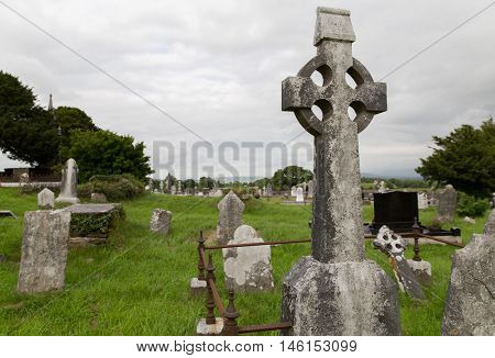 ancient monument and burial concept - old headstones and ruins on celtic cemetery graveyard in ireland