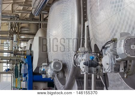Stainless steel vessels and other equipment in workshop of primary grapes processing and primary fermentation in the modern winery