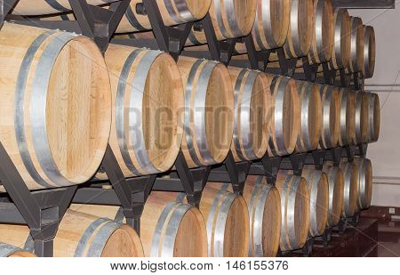 Steel shelving with rows of new oak wine barrels on warehouse in winery
