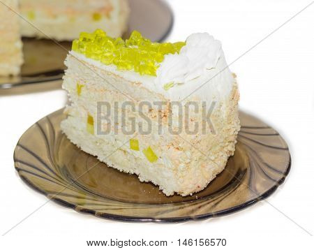 Piece of layered cake decorated with slices of lemon jelly on a dark glass saucer closeup on a light background