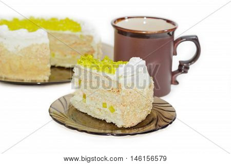Piece of layered cake decorated with slices of lemon jelly on glass saucer against the background of the cup and the rest of the cake
