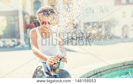 Summer hot day. Cute little girl playing with fountain. Hot weather.