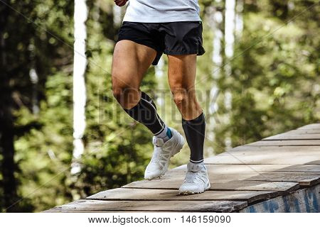 marathon runner running in forest wooden bridge feet in compression socks