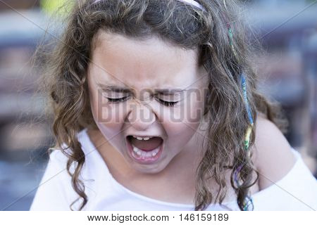 Portrait of curly-haired girl screaming out loud with eyes closed