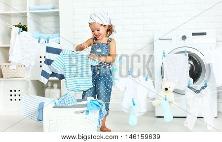 child fun happy little girl to wash clothes and laughs in the laundry room