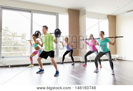 fitness, sport, training, exercising and lifestyle concept - group of people with barbell bars doing squats in gym