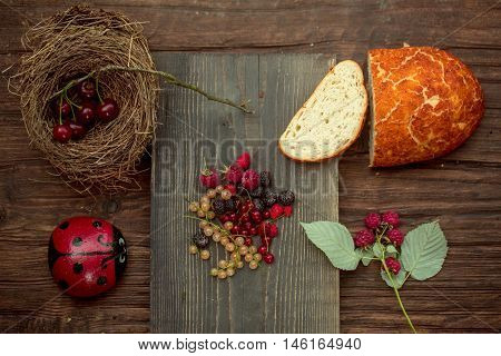 Freshly baked loaf of wheat bread and cut slice on wooden board with red and white currant strawberry blackberry raspberry cherry and painted stone in ladybird or ladybug